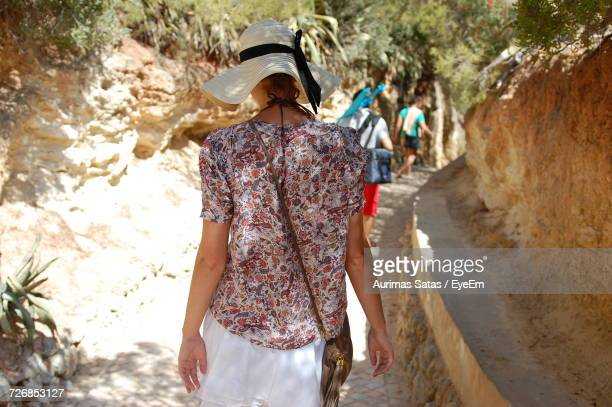 Rear View Of Woman Walking On Footpath