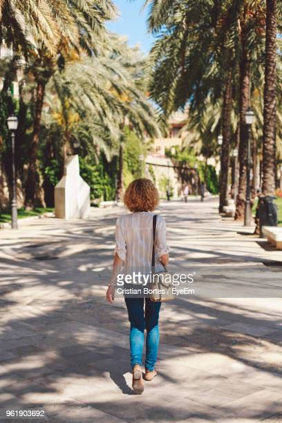 rear view of woman walking on footpath - bortes stock pictures, royalty-free photos & images