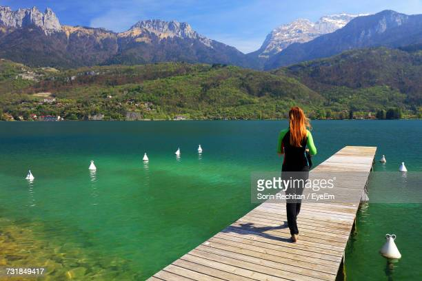 Rear View Of Woman Walking On Jetty Over Lake