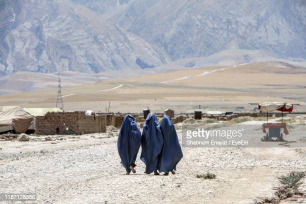 rear view of woman walking on land - afghanistan stock pictures, royalty-free photos & images