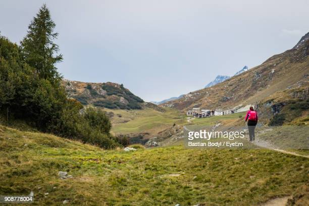 Rear View Of Woman Walking On Mountain Against Cloudy Sky