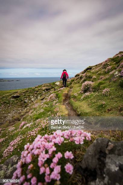 Rear View Of Woman Walking On Mountain By Sea Against Cloudy Sky