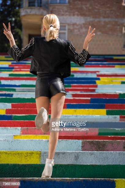 rear view of woman walking on multi colored steps - women in daisy dukes stock photos and pictures
