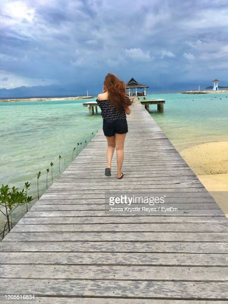 rear view of woman walking on pier at beach against sky - jessa stock pictures, royalty-free photos & images