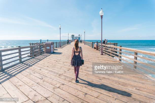 rear view of woman walking on pier over sea against sky - railings stock pictures, royalty-free photos & images