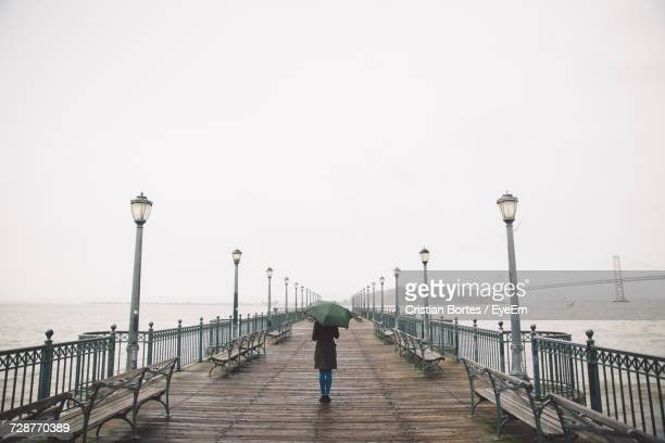 rear view of woman walking on pier - bortes stock pictures, royalty-free photos & images