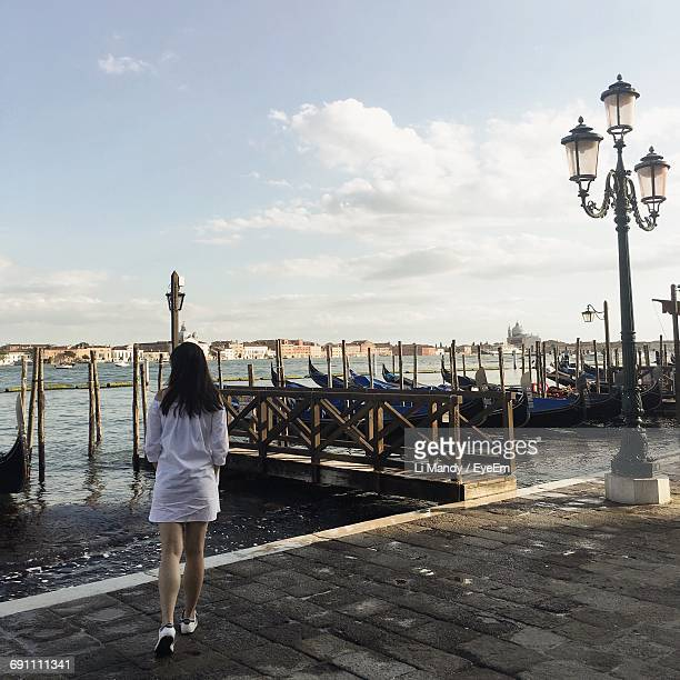 rear view of woman walking on promenade by gondolas moored on grand canal - one young woman only stock pictures, royalty-free photos & images