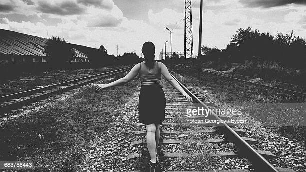 Rear View Of Woman Walking On Railroad Track Against Cloudy Sky During Sunset