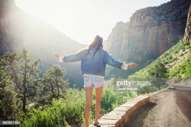 Rear view of woman walking on retaining wall by street against mountains