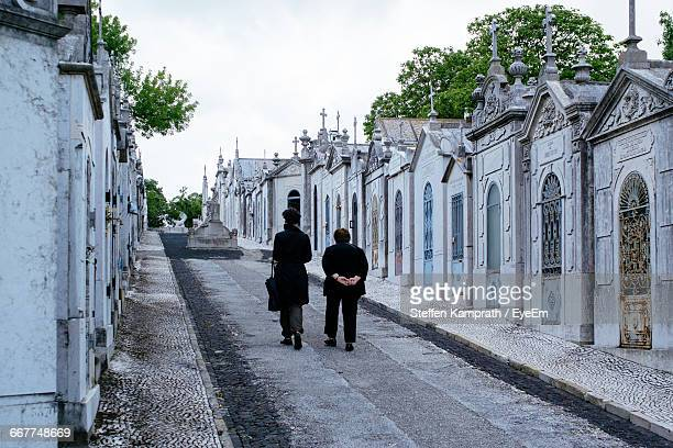 Rear View Of Woman Walking On Road Amidst Tombstones In Cemetery