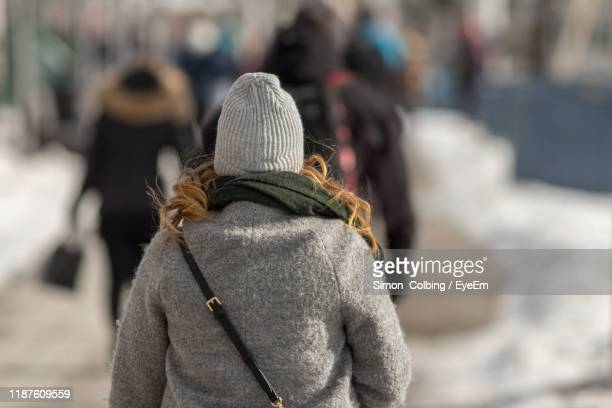 rear view of woman walking on road during winter - colbing stock pictures, royalty-free photos & images