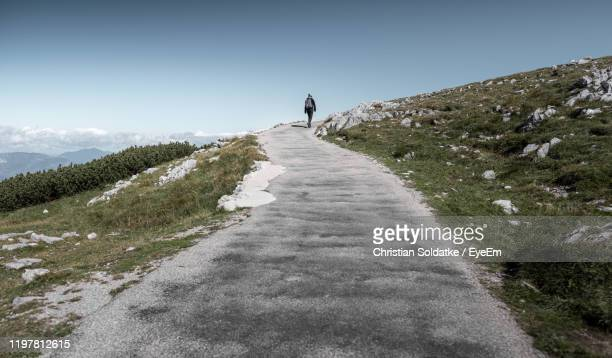 rear view of woman walking on road on hill against sky - christian soldatke stock pictures, royalty-free photos & images