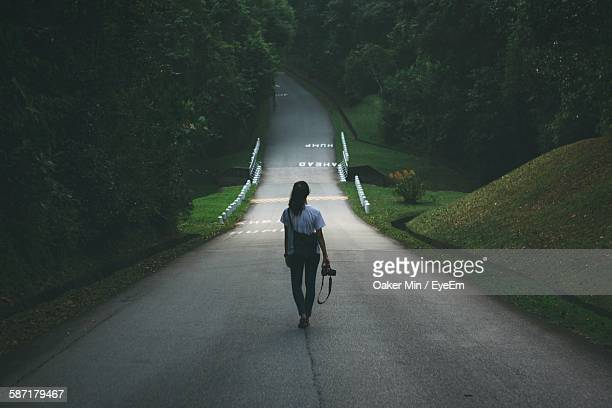 Rear View Of Woman Walking On Road