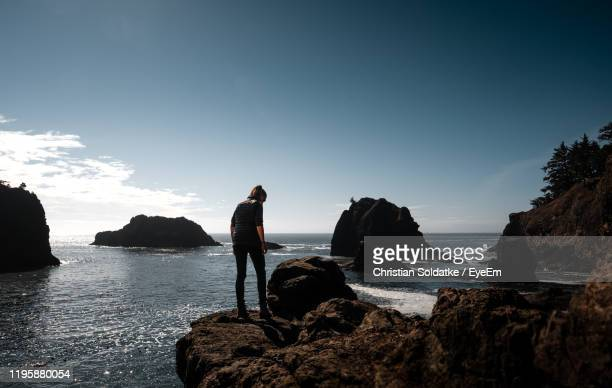 rear view of woman walking on rock by sea against sky - christian soldatke stock pictures, royalty-free photos & images