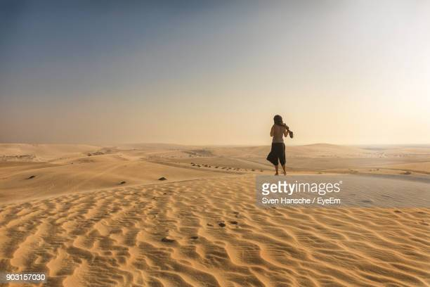 rear view of woman walking on sand at beach against clear sky - qatar fotografías e imágenes de stock