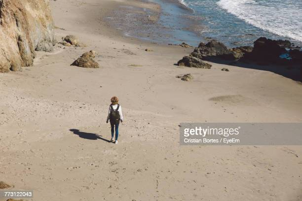Rear View Of Woman Walking On Sand At Beach