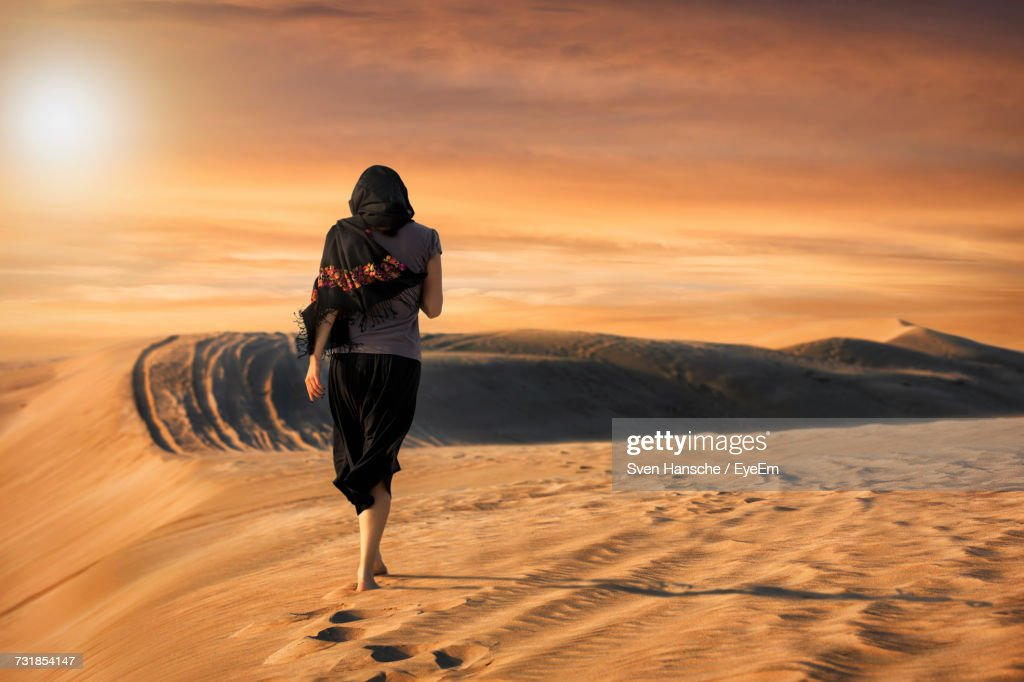 Rear View Of Woman Walking On Sand At Desert Against Sky During Sunset : Stock Photo