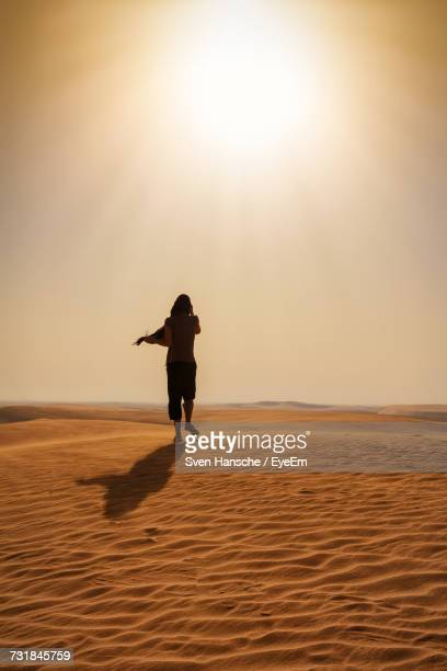 Rear View Of Woman Walking On Sand At Desert Against Sky During Sunny Day