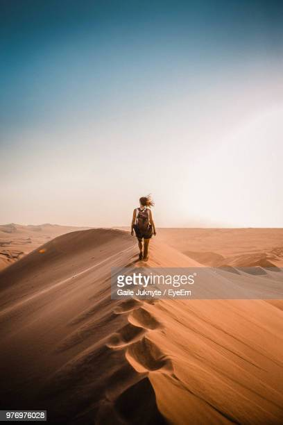 rear view of woman walking on sand dune in desert - avontuur stockfoto's en -beelden