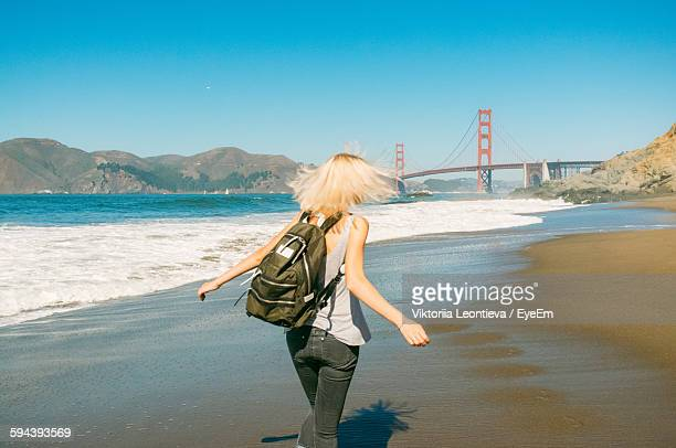 Rear View Of Woman Walking On Shore With Golden Gate Bridge Against Clear Sky