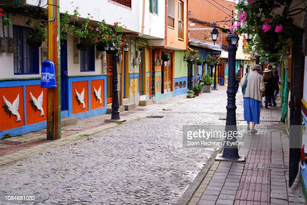 rear view of woman walking on sidewalk in city - medellin colombia stock pictures, royalty-free photos & images