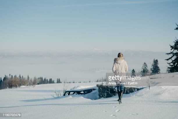 Rear View Of Woman Walking On Snow Covered Land Against Sky During Winter