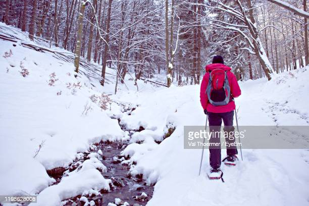 rear view of woman walking on snow covered land - val thoermer stock-fotos und bilder
