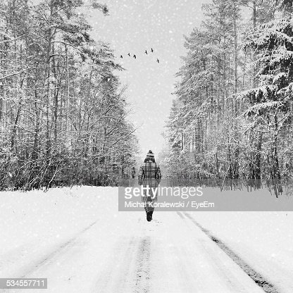 Rear View Of Woman Walking On Snow Covered Road In Winter
