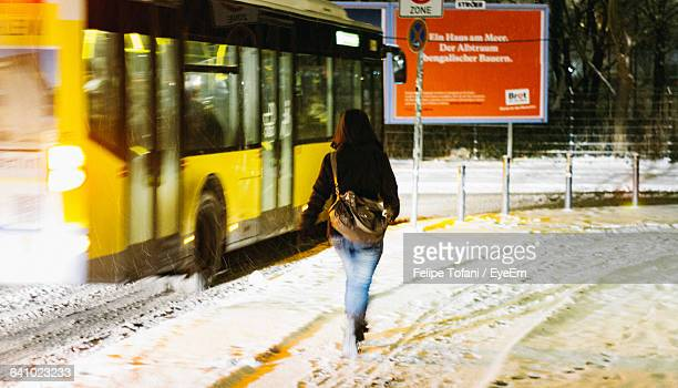 Rear View Of Woman Walking On Snow Covered Street