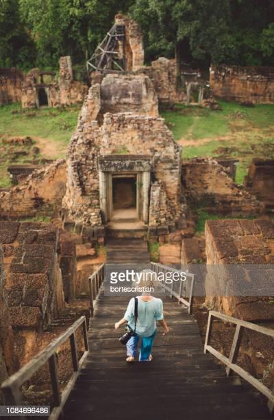 rear view of woman walking on steps against old ruins - bortes stock-fotos und bilder