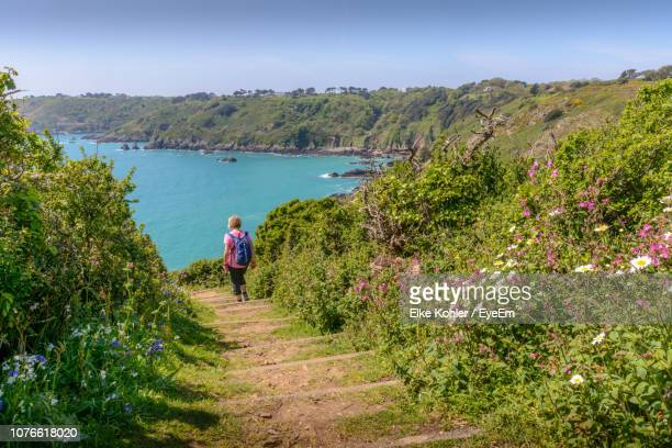 rear view of woman walking on steps towards sea at beach - isola di guernsey foto e immagini stock