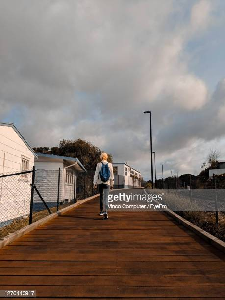 rear view of woman walking on street against sky - whangarei heads stock pictures, royalty-free photos & images