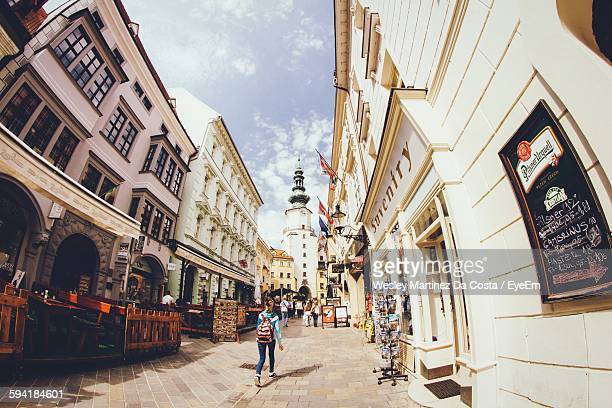 rear view of woman walking on street amidst buildings - bratislava stock pictures, royalty-free photos & images