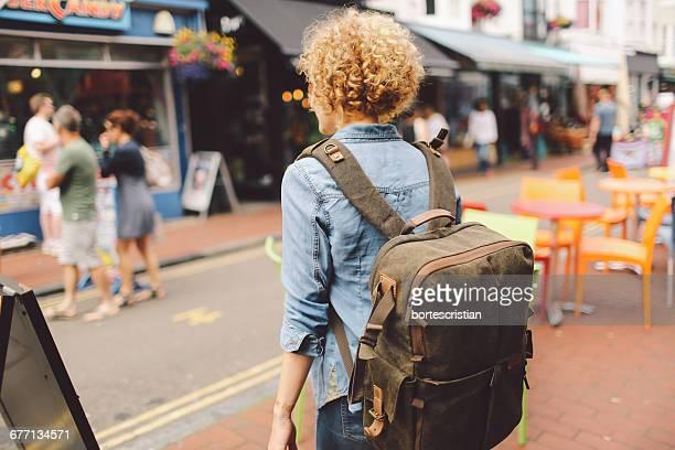 rear view of woman walking on street in city - bortes stock-fotos und bilder
