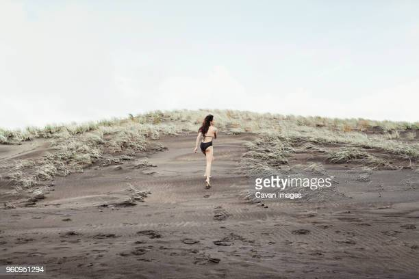Rear view of woman walking on wet sand at Bethells Beach against clear sky