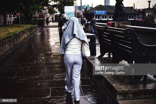 Rear View Of Woman Walking On Wet Street During Monsoon