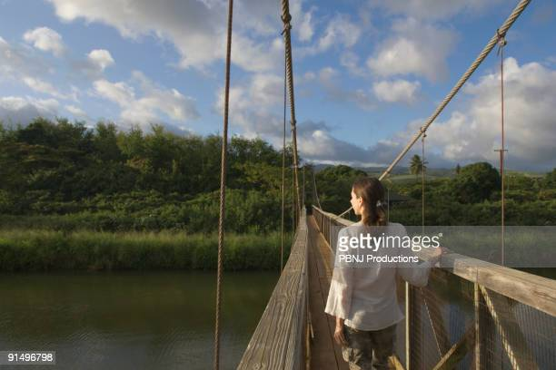Rear view of woman walking on wooden footbridge