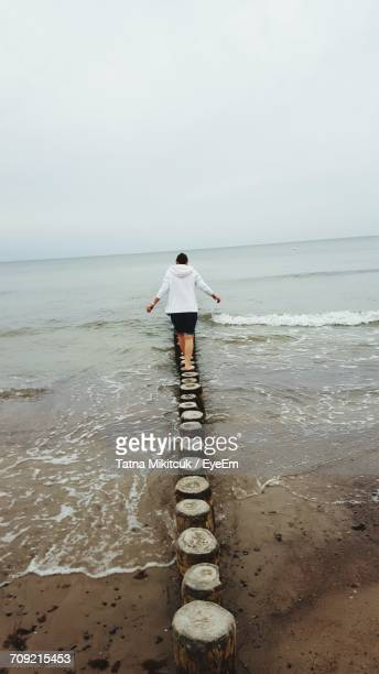 Rear View Of Woman Walking On Wooden Post At Beach