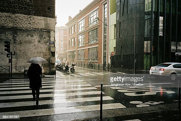 Rear View Of Woman Walking On Zebra Crossing At Wet Street By Buildings During Monsoon