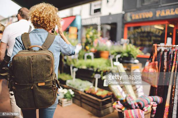 Rear View Of Woman Walking Through Street Market Stalls In City