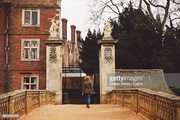 rear view of woman walking towards building gate - bortes stock pictures, royalty-free photos & images