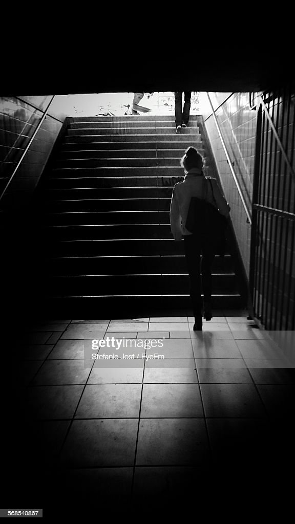 Rear View Of Woman Walking Towards Steps In Subway : Stock Photo