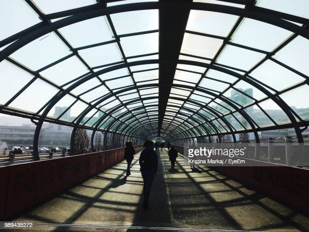 rear view of woman walking under bridge - bielefeld stock pictures, royalty-free photos & images