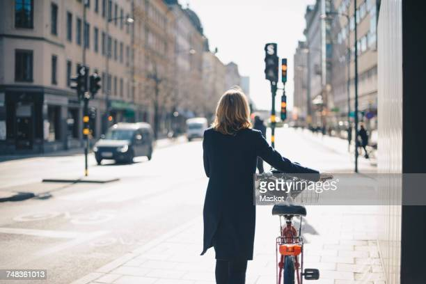Rear view of woman walking with bicycle on sidewalk in city during sunny day