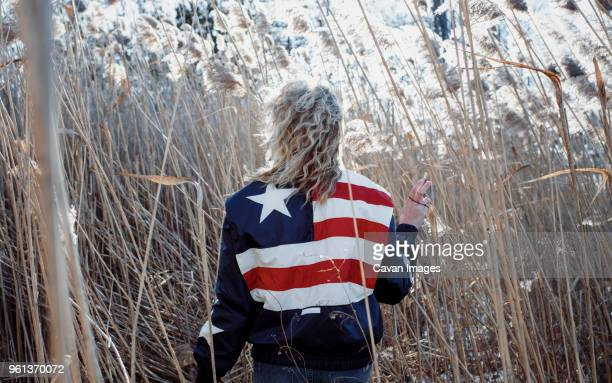 Rear view of woman wearing American Flag jacket while walking amidst plants on field