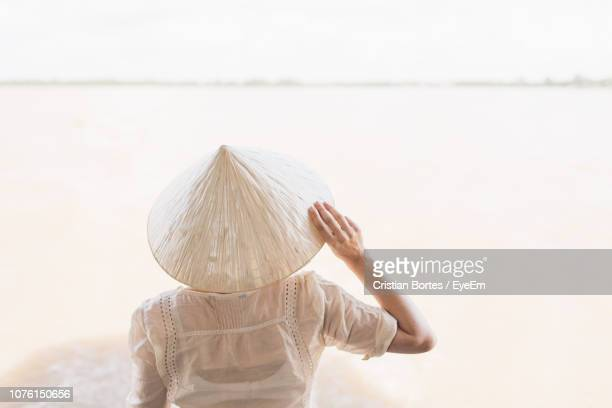 Rear View Of Woman Wearing Asian Style Conical Hat At Beach