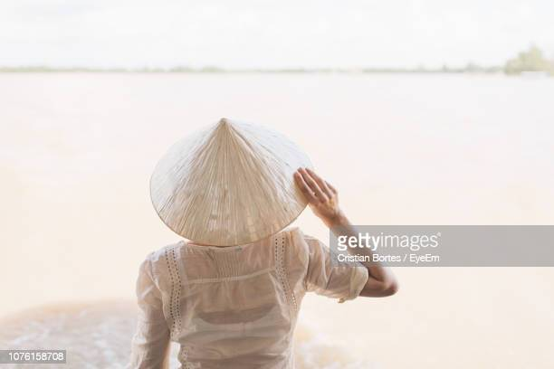 Rear View Of Woman Wearing Asian Style Conical Hat By Lake