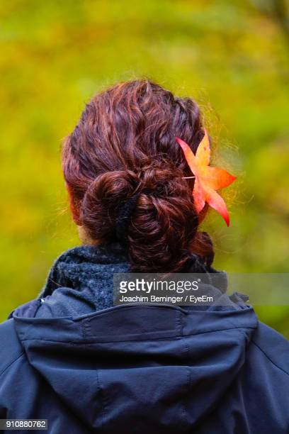 Rear View Of Woman Wearing Autumn Leaf