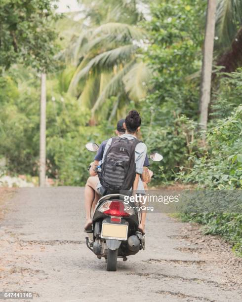 rear view of woman wearing backpack on back of moped - moped stock photos and pictures