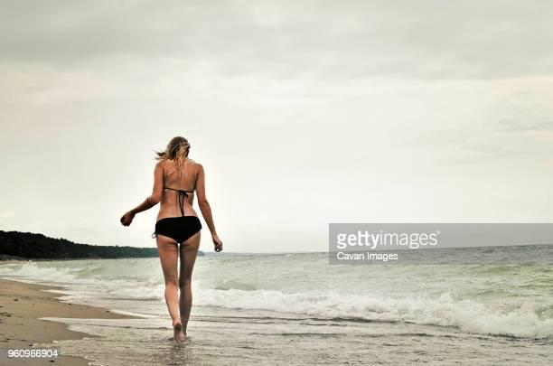 Rear view of woman wearing bikini walking at beach against clear sky